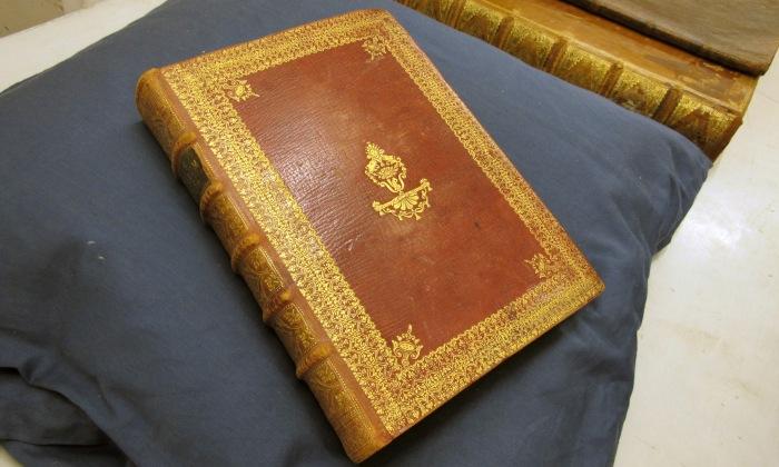 rött bokband med guldpressad dekor