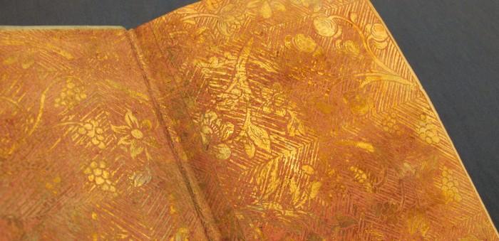 försättsblad i rött och guld med växtmotiv